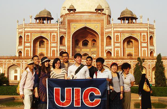 Students holding a UIC flag in front of a mosque in an unknown foreign country