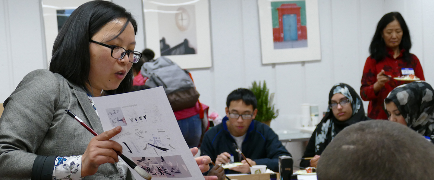 An instructor shows a group how to write in Chinese calligraphy