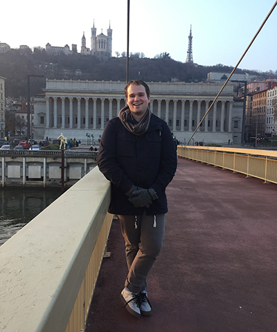 Dalton Day stands on a bridge in Lyon, France with monuments in the background