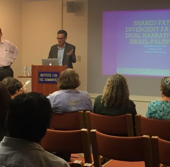 Ibish & Myers stand at a podium in the Humanities Institute