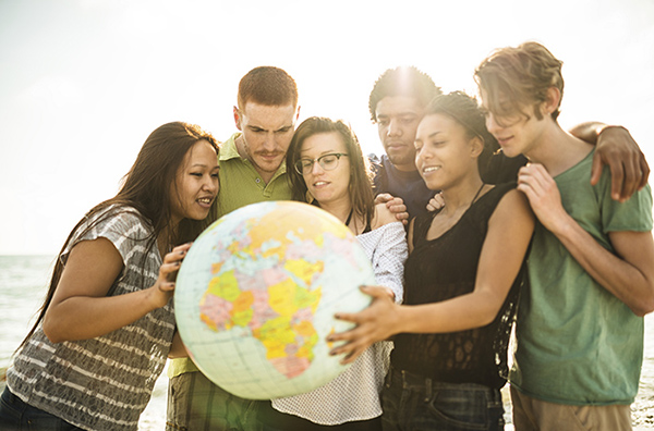 diverse mixed group of students hold and look at a globe