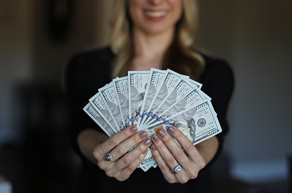 a blond white woman holds out a fan of $100 bills