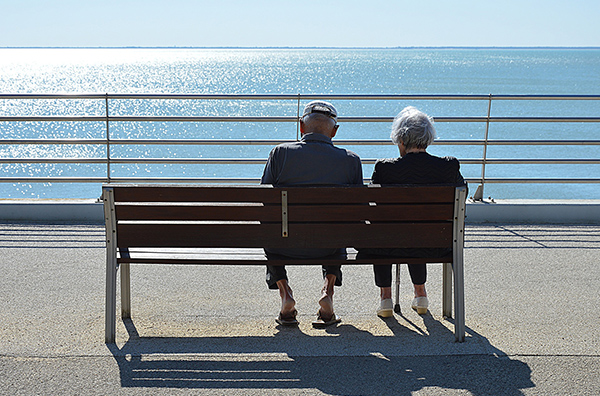 old couple sitting on a bench at the beach seen from behind